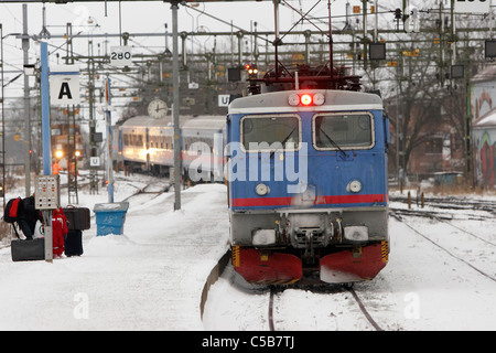 Train leaving the station platform in winter - Stock Photo