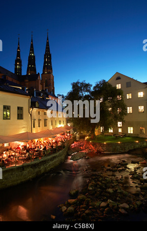 River by houses with cathedral against clear blue sky at dusk, Uppsala, Sweden - Stock Photo