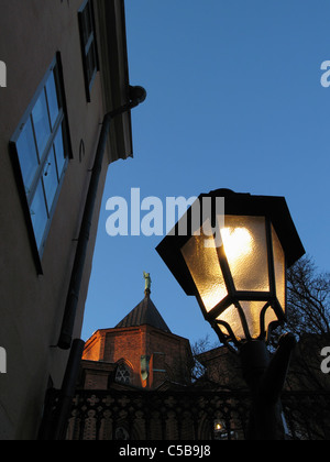 Low angle view of lit streetlight and Uppsala Cathedral against clear blue sky at night - Stock Photo