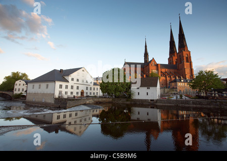 Cathedral and houses reflecting in water against sky at Uppsala, Sweden - Stock Photo