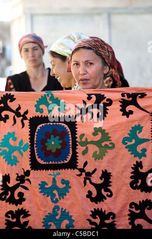 Textile vendor with embroidered suzani textile, Urgut market, Samarkand, Uzbekistan - Stock Photo