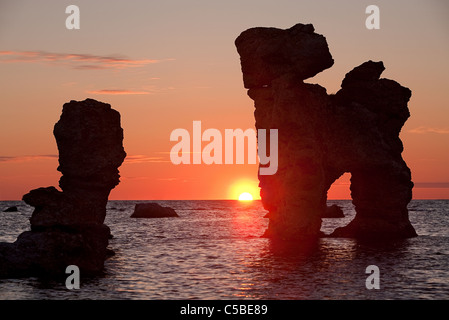 Silhouette rock formations in peaceful sea at sunset - Stock Photo