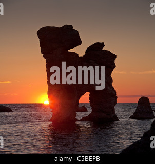 Scenic shot of silhouette rauker in sea against dramatic sky at sunset - Stock Photo