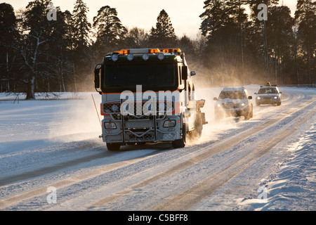 Tow truck and cars on snow covered road with trees in the background - Stock Photo