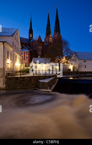 Uppsala cathedral against clear blue sky with Fyrisån in the foreground at night - Stock Photo