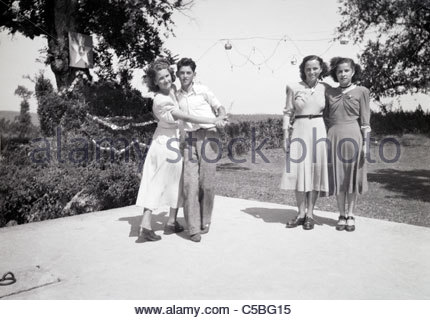 young couple and two girls on the dancing floor in a rural environment - Stock Photo