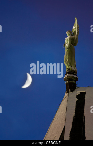 Low angle view of angel statue and moon against clear blue sky - Stock Photo