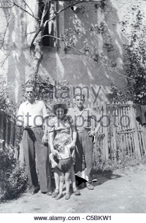 family with friend and young child posing outside the house rural France 1950s - Stock Photo