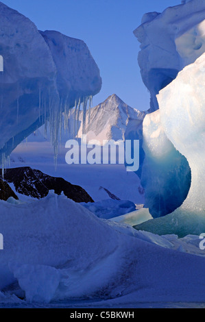 Mount Herschel framed by icicles and ice bergs from near Cape Hallett northern Ross Sea Antarctica - Stock Photo