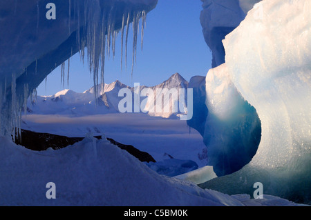 Mount Herschel framed by icicles and ice berg from Cape Hallett northern Ross Sea Antarctica - Stock Photo