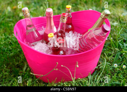 Cooling bottles  with icecubes in a huge pink plastic container in the garden - Stock Photo