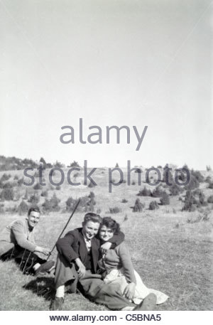 young couple in a field with other man playing in the background - Stock Photo