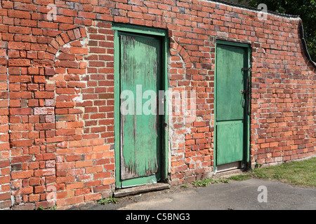 Two green doors in an old brick wall - Stock Photo