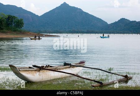 A traditional fishing boat on the shore of Kandalama lake. Sri Lanka. - Stock Photo