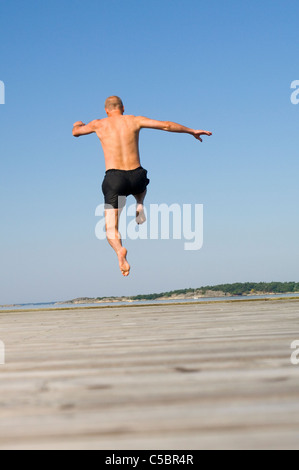Rear view of a shirtless man jumping on sand against clear blue sky - Stock Photo