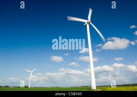 Low angle view of wind turbines on peaceful landscape against the sky - Stock Photo