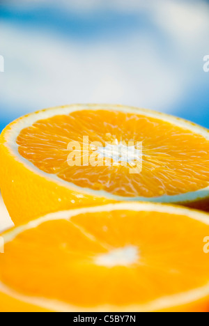 Close-up of fresh orange in two halves against blurred background - Stock Photo
