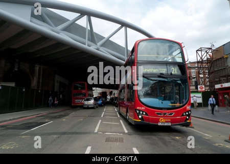 A red double-decker 21 bus destined for Lewisham passing under Network Rail new railway Viaduct Bridge at London - Stock Photo