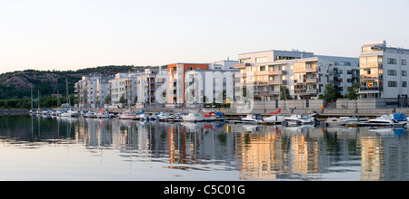Panoramic shot of buildings with reflection in water against clear sky at Sannegårdshamnen - Stock Photo