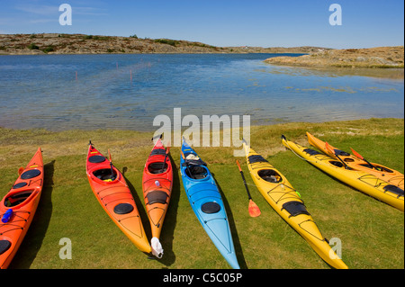 Several kayaks on grass by the calm sea - Stock Photo