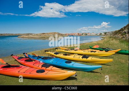 Several kayaks on grass by the calm sea below clouds in the sky - Stock Photo