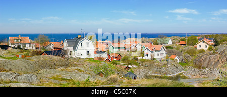 Panoramic shot of landscape and houses with sea in the background - Stock Photo