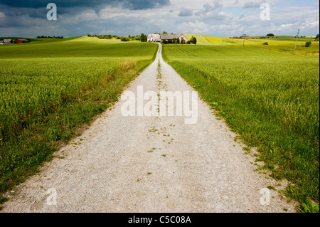 View of empty gravel road along the landscape with clouds in the background - Stock Photo