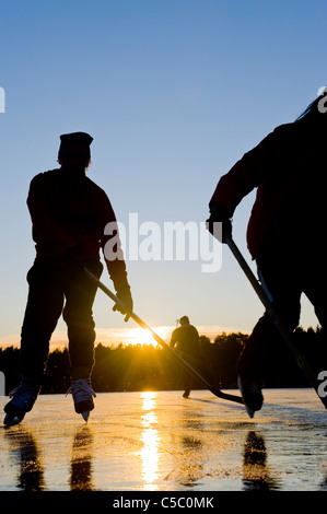 Two silhouette skaters on the lake against clear blue sky in the background at sunset - Stock Photo