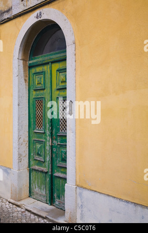 Old Wooden Door On A Yellow Building; Cascais, Portugal - Stock Photo