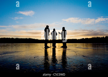 Three silhouette people standing on the ice landscape against scenic sky at dusk - Stock Photo