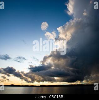 Scenic shot of rain clouds over a peaceful sea - Stock Photo