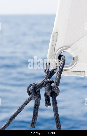 Close-up of sail ship rigging against the water - Stock Photo