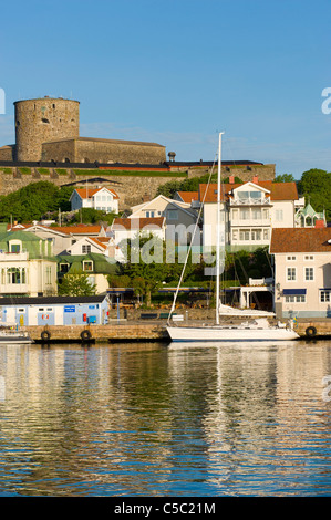 Houses in distance against clear blue sky at Marstrand with reflection in water, Bohuslän, Sweden - Stock Photo