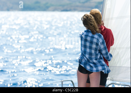 Rear view of a couple in the bow of the sailboat with glittering sea in the background - Stock Photo