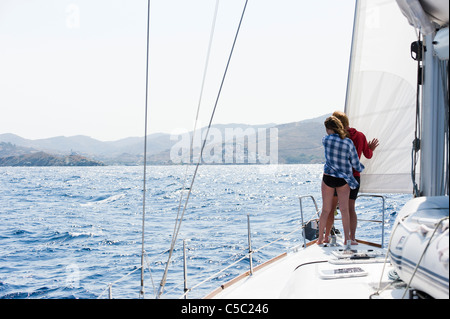 Rear view of a couple in the bow of a sailboat overlooking the Aegean sea - Stock Photo