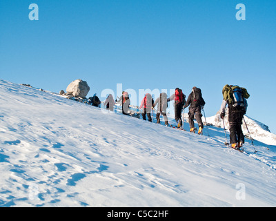 Rear view of people skiing up the slope against clear blue sky - Stock Photo