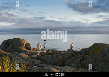 Mid distance of a family walking on rocks towards the sea - Stock Photo