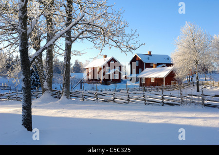 Red houses and trees against clear sky in winter landscape - Stock Photo