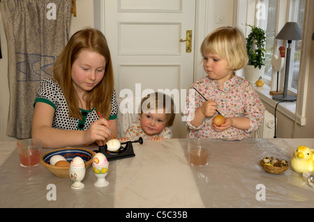 Three girls coloring Easter eggs at table in the house - Stock Photo