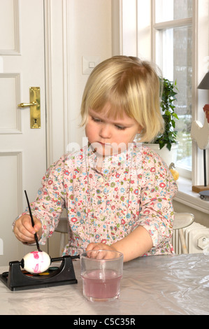 Little girl painting Easter eggs at table in the house - Stock Photo