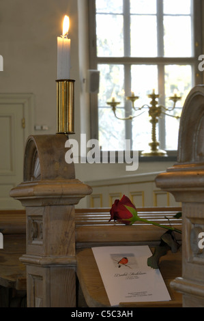 Close-up of a rose and card on pew by lit candle in the church - Stock Photo