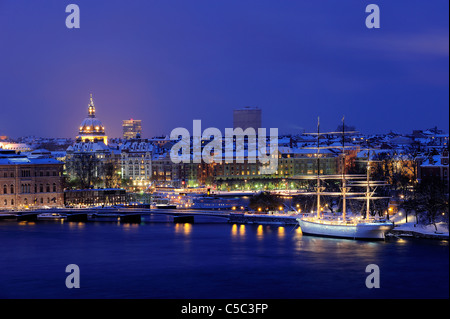 Af Chapman with illuminated buildings and placid lake in foreground, Stockholm, Sweden - Stock Photo