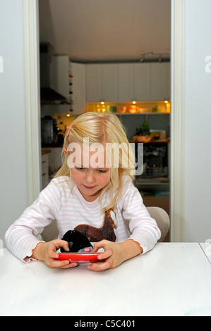 Little girl playing on the smart phone at home - Stock Photo