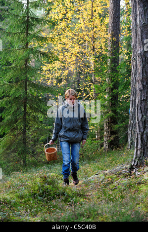 Woman walking with mushroom basket in the woods - Stock Photo