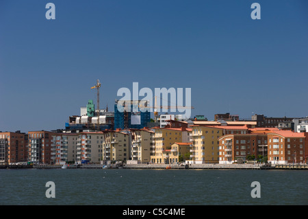 Peaceful sea with buildings in the background against clear blue sky - Stock Photo