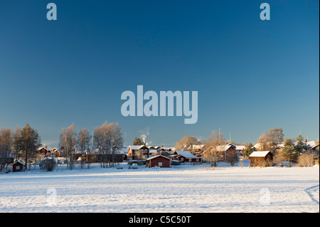 Distance shot of houses and trees against clear blue sky in winter at Dalarna, Sweden - Stock Photo
