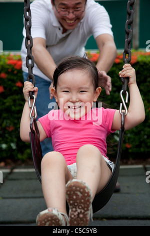Laughing little girl on swing with her father - Stock Photo