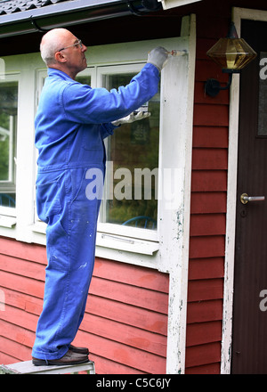 Side view of an elderly man in blue overall painting cottage window - Stock Photo