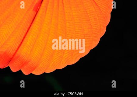 Chinese paper lantern in illuminating orange light at night - Stock Photo
