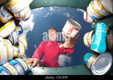 man throwing metal can into green recycling bin for recycling - Stock Photo